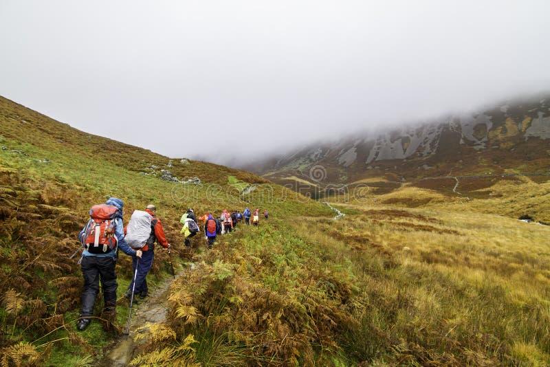 En grupp av fotvandrare i den Snowdonia nationalparken i Wales royaltyfri foto
