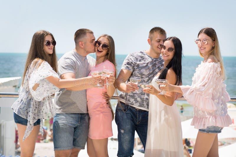 En grupp av glade vänner som kopplar av på en semester Nätta flickor och starka män på en bakgrund för blå himmel kamratskap arkivbilder