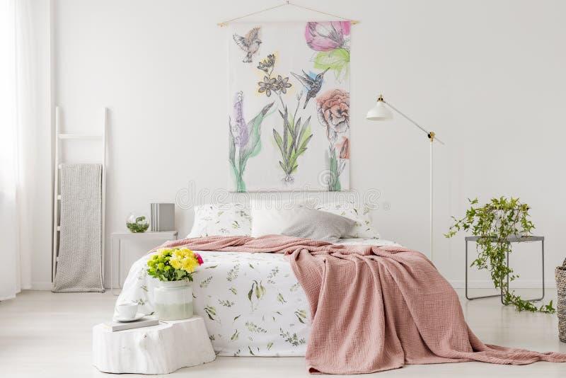 En grupp av gula nya snittblommor i en ljus sovruminre med en filt för linne och för persika för iklädd vit för säng Tyg på th royaltyfri bild