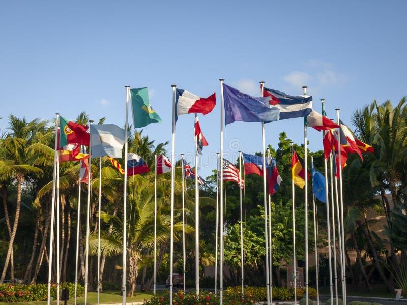 En grupp av internationella flaggor på flaggapoler fotografering för bildbyråer