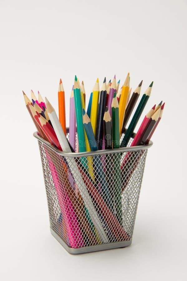 En grupp av kulöra blyertspennor i ettexponeringsglas på en vit backgro royaltyfri bild