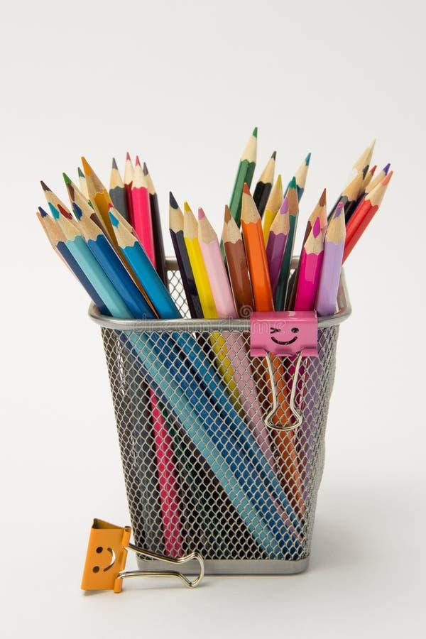 En grupp av kulöra blyertspennor i ettexponeringsglas på en vit backgro royaltyfri foto