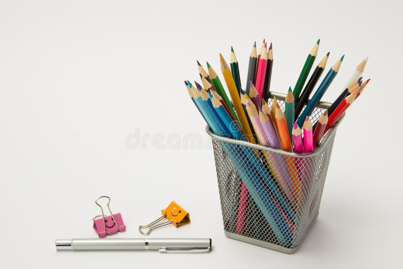 En grupp av kulöra blyertspennor i ettexponeringsglas på en vit backgro royaltyfria bilder
