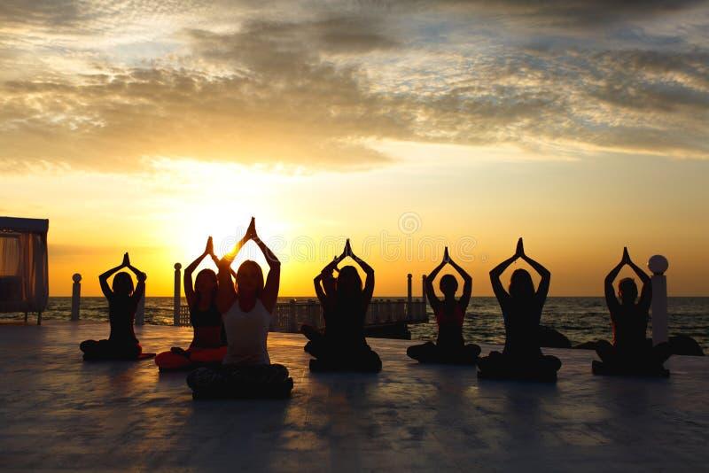 En grupp av kvinnor som gör yoga på soluppgång nära havet arkivfoton