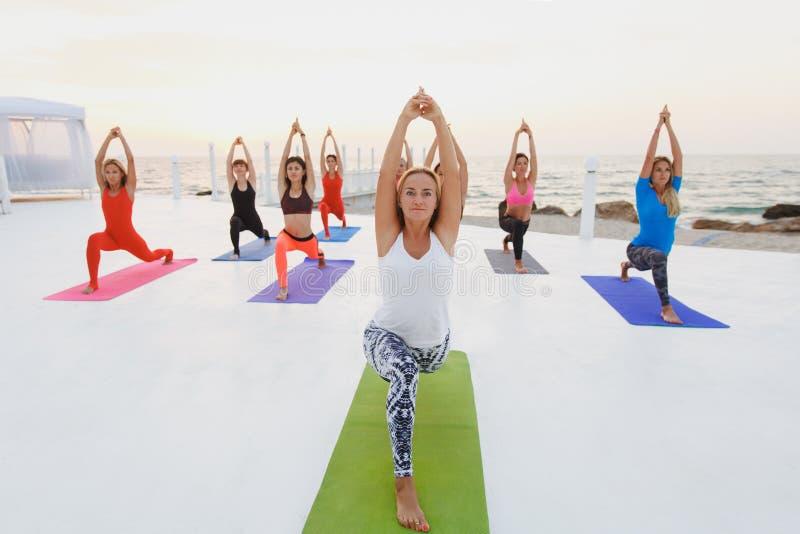 En grupp av kvinnor som gör yoga på soluppgång nära havet royaltyfria foton