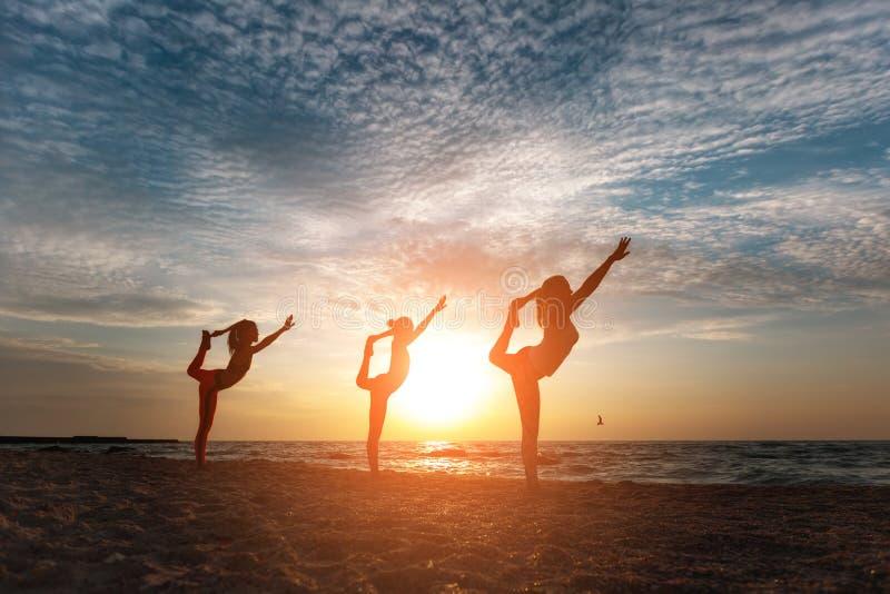 En grupp av kvinnor som gör yoga på soluppgång nära havet arkivfoto
