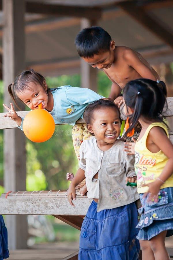 En grupp av lyckliga en khmerbarn som spelar i en by nära Mekong River, Cambodja royaltyfri foto