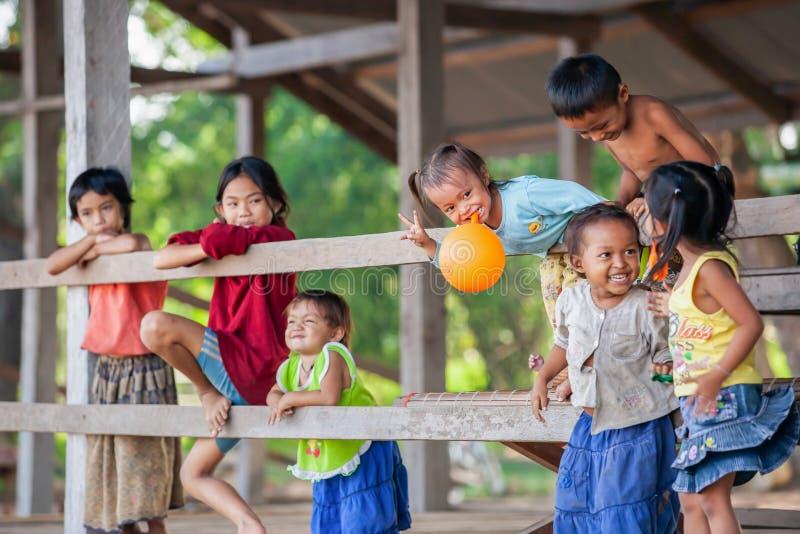 En grupp av lyckliga en khmerbarn som spelar i en by nära Mekong River, Cambodja arkivfoton