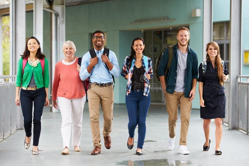 En grupp av lyckliga lärare som går i en skolakorridor royaltyfri foto