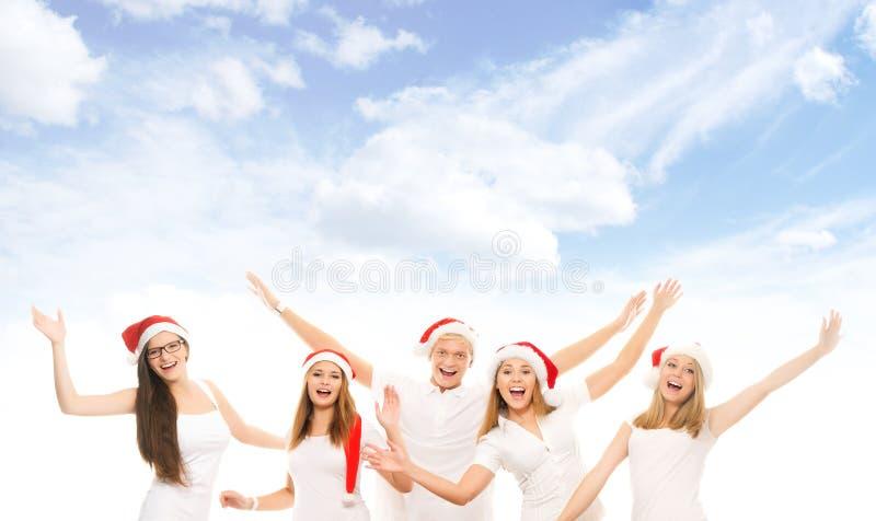 En grupp av lyckliga och emotionella tonåringar i julhattar arkivbild