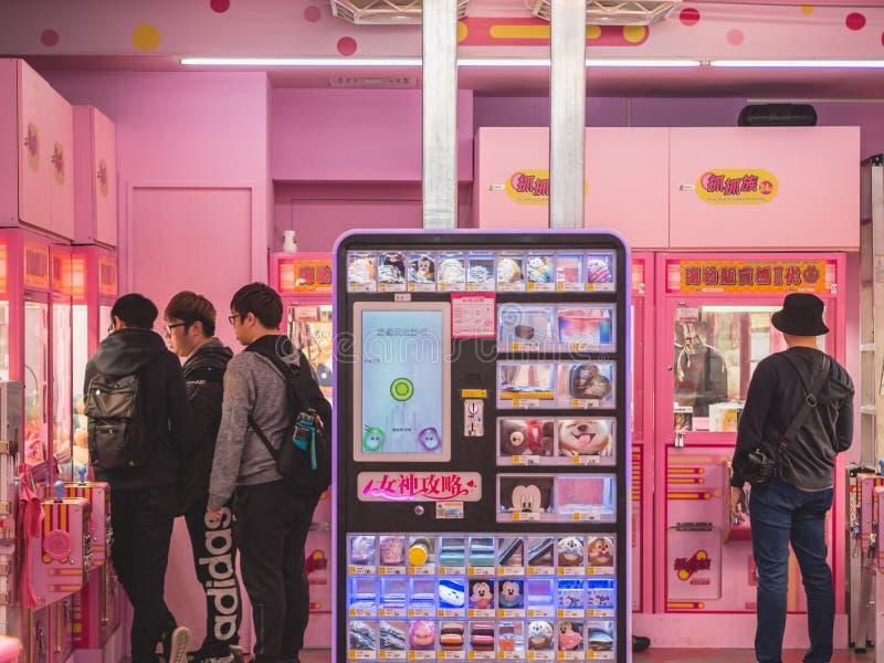 En grupp av män som spelar en Arcade Claw Crane Game på området för Ximending ungdomshopping royaltyfri bild