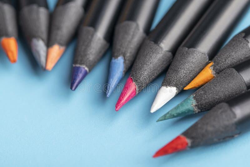 En grupp av m?ngf?rgade tr?blyertspennor i ett svart fall mot en bl? bakgrund royaltyfria bilder
