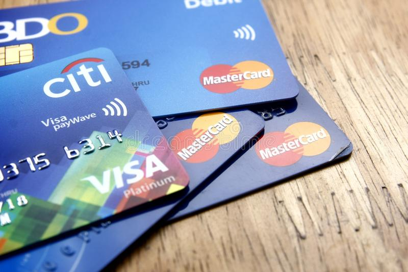 En grupp av Mastercard och visumkreditkortar fördelade på en trätabell arkivbild