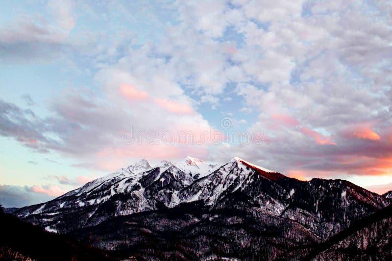 En grupp av moln i himlen över en snö täckte berget arkivfoto