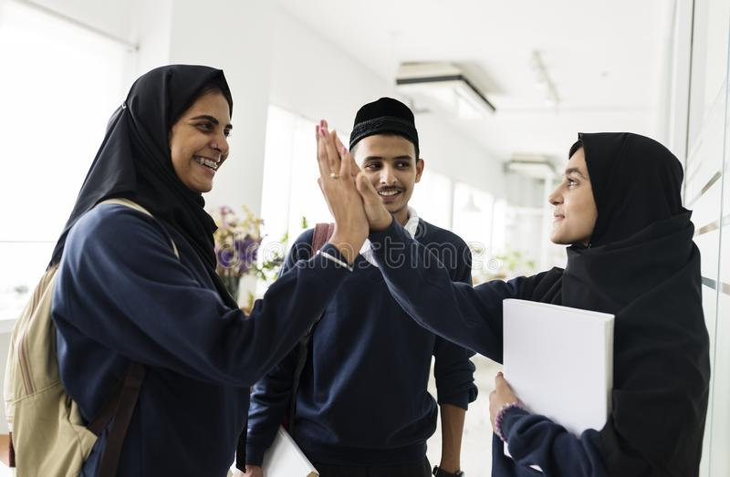 En grupp av muslimska studenter som gör hi-5 royaltyfri foto