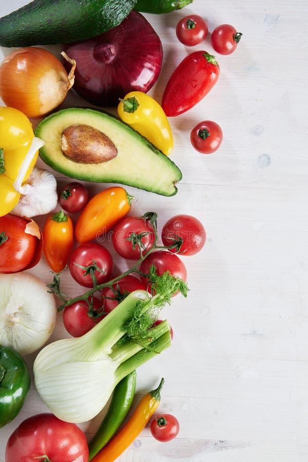 En grupp av nya olika säsongsbetonade gröna grönsaker avokado, fänkål, vitlök, lök, tomat, röd gul peppar från över royaltyfri fotografi