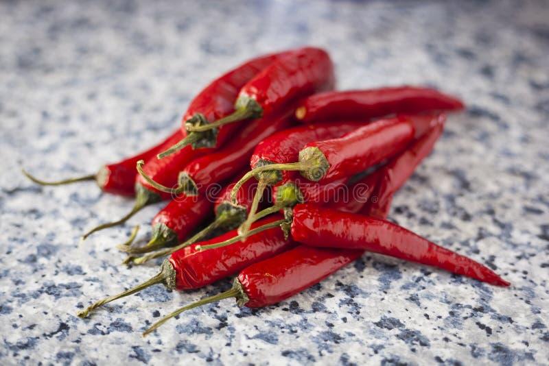 En grupp av nya röda peppar på en köksbordbakgrund arkivfoton