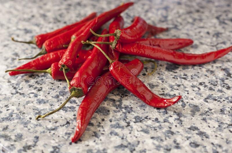 En grupp av nya röda peppar på en köksbordbakgrund royaltyfri foto