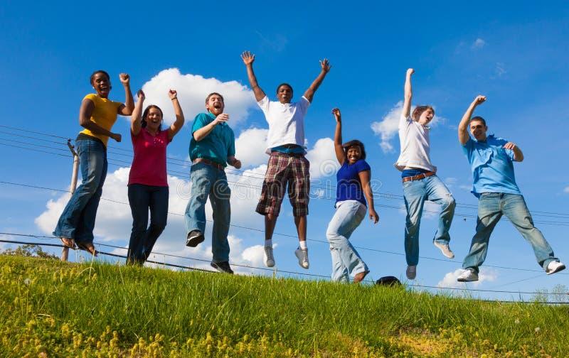 En grupp av olika högskolestudenter/vänner som hoppar i luften arkivfoton