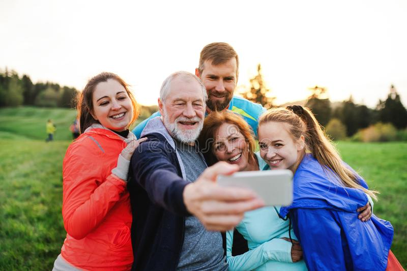 En grupp av passformen och aktivt folk som vilar, når att ha gjort övning i natur som tar selfie royaltyfri bild