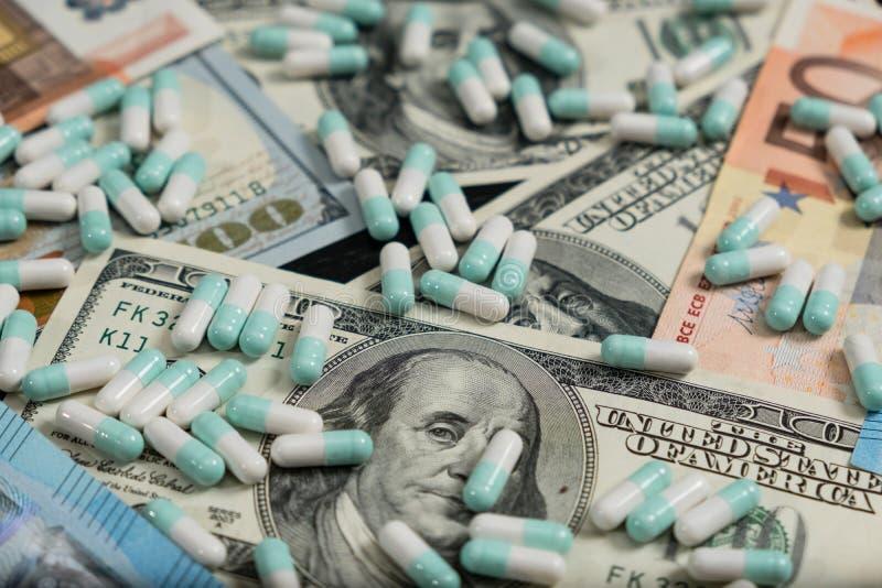 En grupp av preventivpillerar och minnestavlor på euro- och dollarsedlar royaltyfria foton