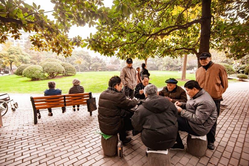 En grupp av spela kort för äldre kinesiska män i parkerar royaltyfri bild
