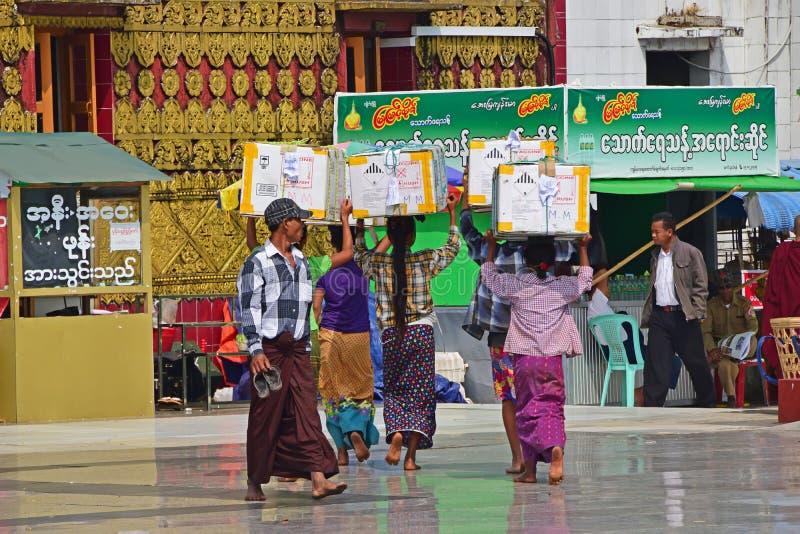 En grupp av strävsamma Burmese kvinnor och män som överst bär skurkrollaskar av deras huvud royaltyfri fotografi