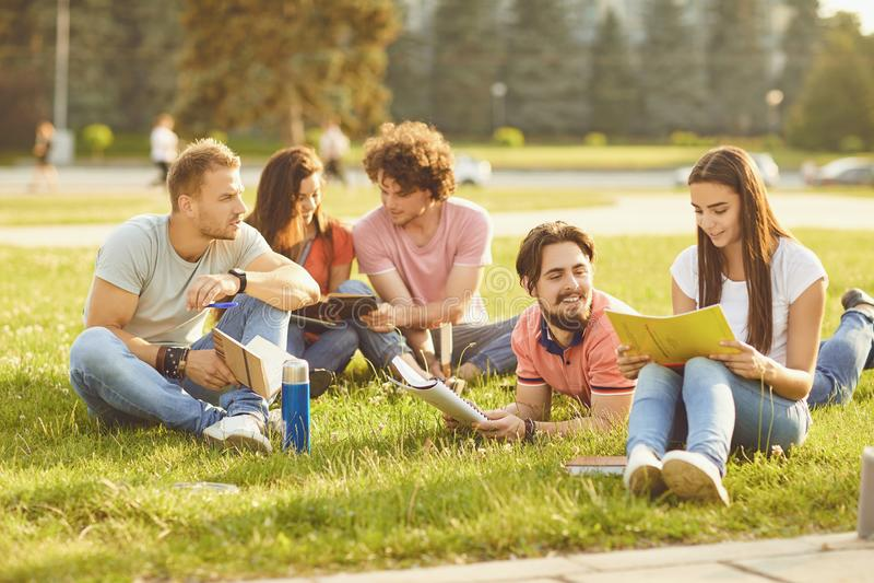 En grupp av studerande böcker för studenter som sitter i en stad, parkerar royaltyfri bild