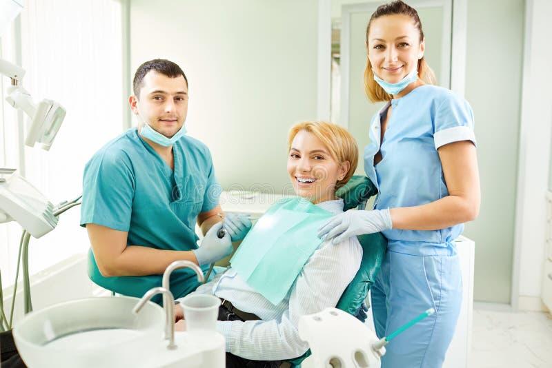 En grupp av tandläkare och en tålmodig flicka royaltyfri bild