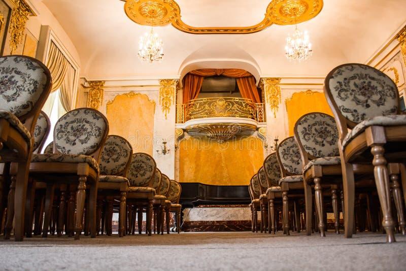 En grupp av tappningträstolställningar i flera rader i ett stort gammalt rum med en lyxig inre tom salong i royaltyfri foto