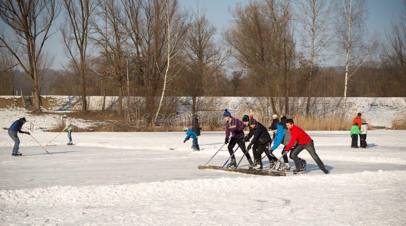 En grupp av tonåringar gör ren isyttersidan, innan den spelar ishockey royaltyfria foton