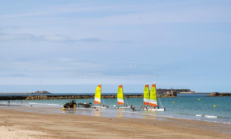 En grupp av tonåringar med instruktörer förbereder sig att segla på en segla katamaran på stranden i Cherbourg, Frankrike fotografering för bildbyråer
