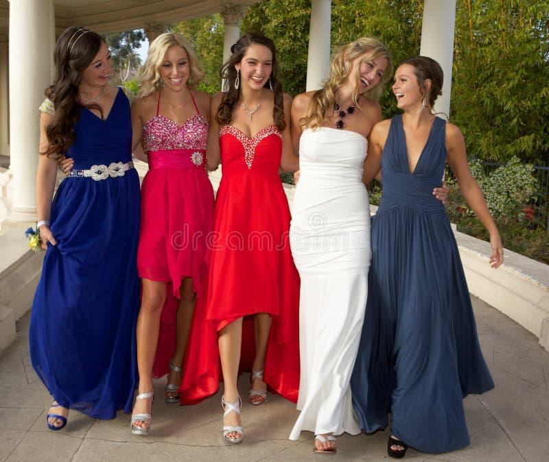En grupp av tonårs- flickor som går i deras studentbal, klär fotografering för bildbyråer