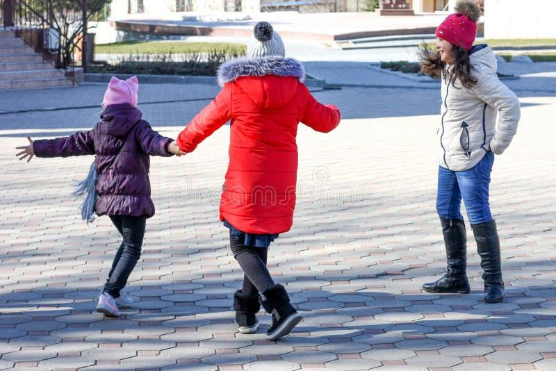 En grupp av tre lyckliga tonårs- flickor på en solig dag som omkring bedrar i gården royaltyfri fotografi