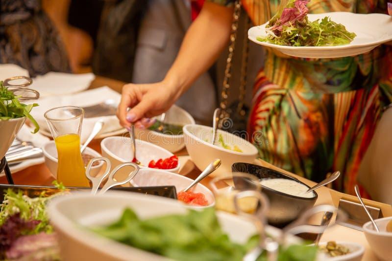 En grupp av turister äter middag alfreskomålningen En kvinna lägger mat bufferten royaltyfri bild