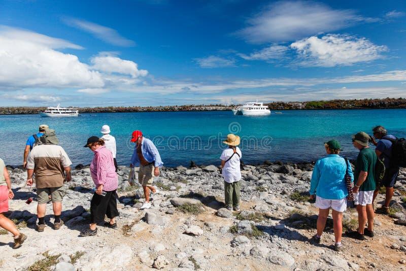 En grupp av turister som besöker Isla Plaza Sur, retur till deras bo arkivfoto