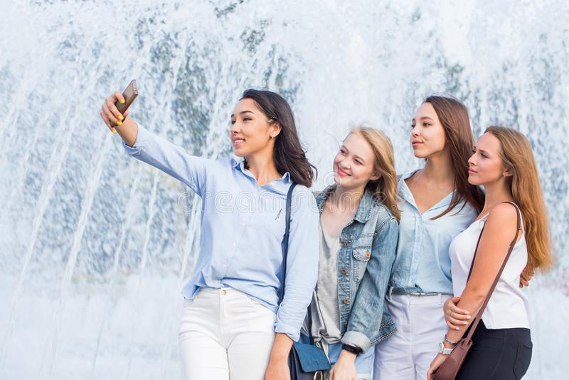En grupp av unga attraktiva flickor av studenter tar en selfie på bakgrunden av en härlig springbrunn royaltyfri fotografi