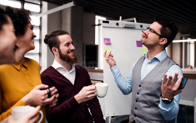 En grupp av unga businesspeople med koppen kaffe som i regeringsställning står och att ha gyckel arkivfoto