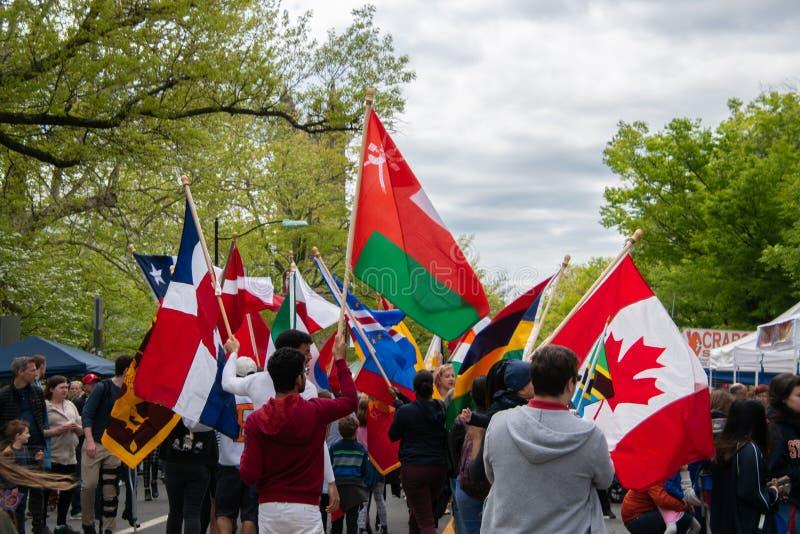 En grupp av unga högskolestudenter som ståtar ner en huvudsaklig gata som rymmer flaggor av olika länder royaltyfri bild