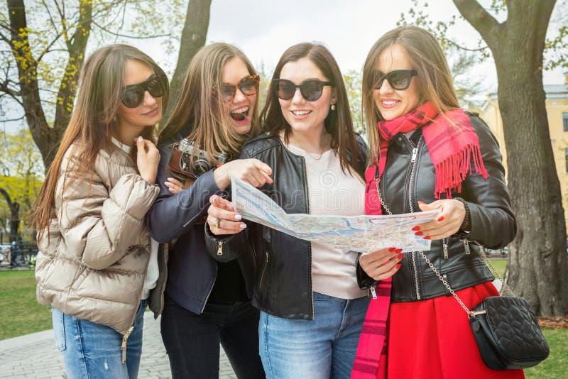 En grupp av unga kvinnliga turister s?ker efter dragningar i en europeisk stad p? ?versikten H?rliga fyra som ?r gladlynta och arkivfoton