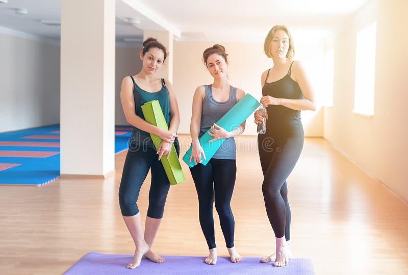 En grupp av unga kvinnor med mats i deras händer som poserar för kameran Begreppet av sportlivsstilen, gymnastik och yoga close fotografering för bildbyråer