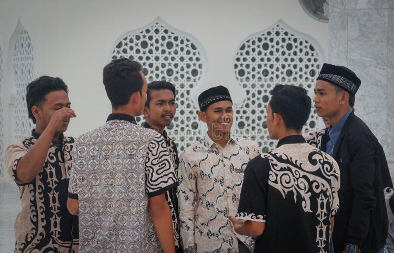 En grupp av unga muslimska asiatiska män i härliga skjortor står nära väggarna av moskén arkivfoto