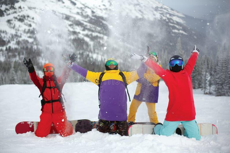 En grupp av unga snowboarders som tycker om det insnöat vintersemesterorten Sheregesh arkivfoton