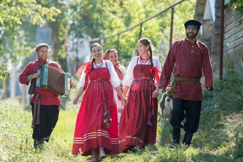 En grupp av ungdomari rysk medborgare kostymerar att gå runt om byn arkivfoto