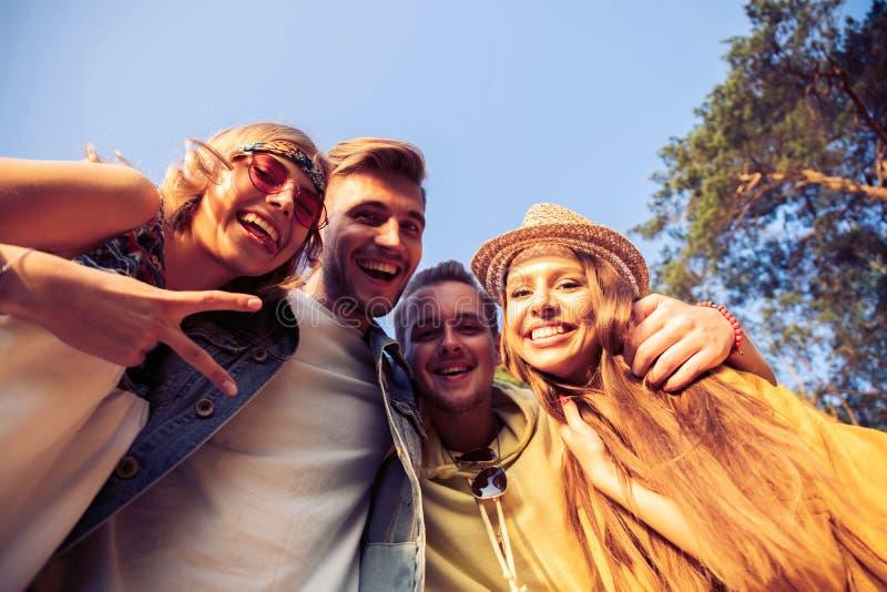 En grupp av ungdomarvänner gör selfies utanför Sommar semester, gyckel, kamratskapbegrepp royaltyfri bild