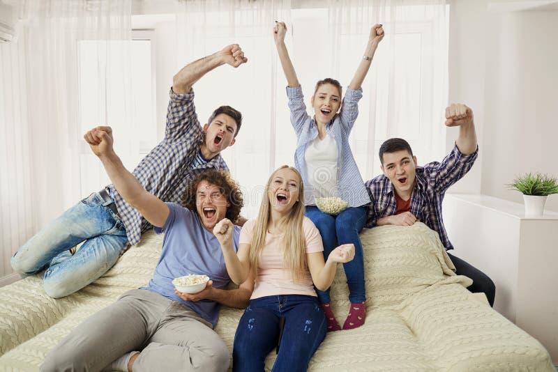 En grupp av vänner av fans som håller ögonen på ett sportTVsammanträde på en sof arkivbild