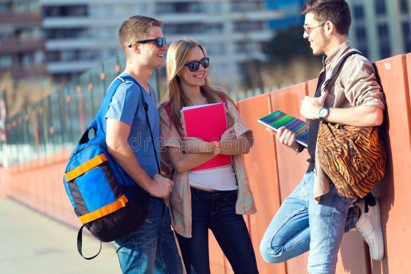 En grupp av vänner som talar i gatan efter grupp fotografering för bildbyråer