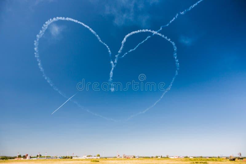 En grupp av yrkesmässiga piloter av flygplan av kämpar på en solig klar dag visar trick i den blåa himlen som drar en romantisk h arkivfoto