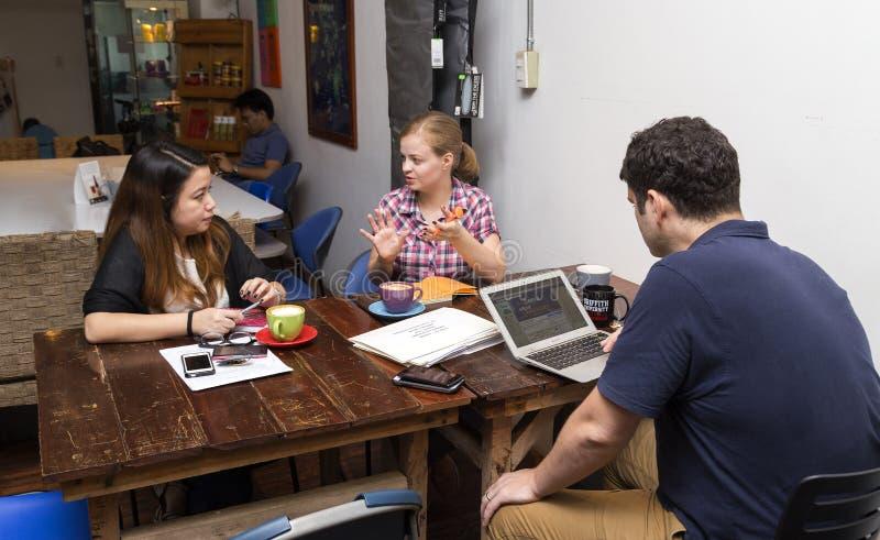 En grupp människor att diskutera idéer i ett kafé, tillfälligt affärsmöte arkivfoto