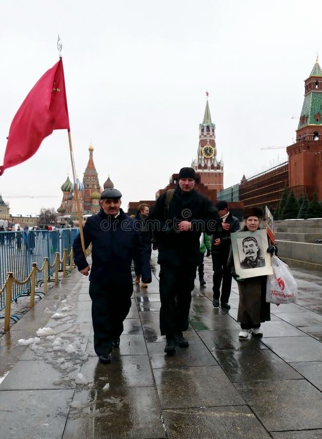 En grupp människor med en stående av Joseph Stalin på röd fyrkant royaltyfri foto